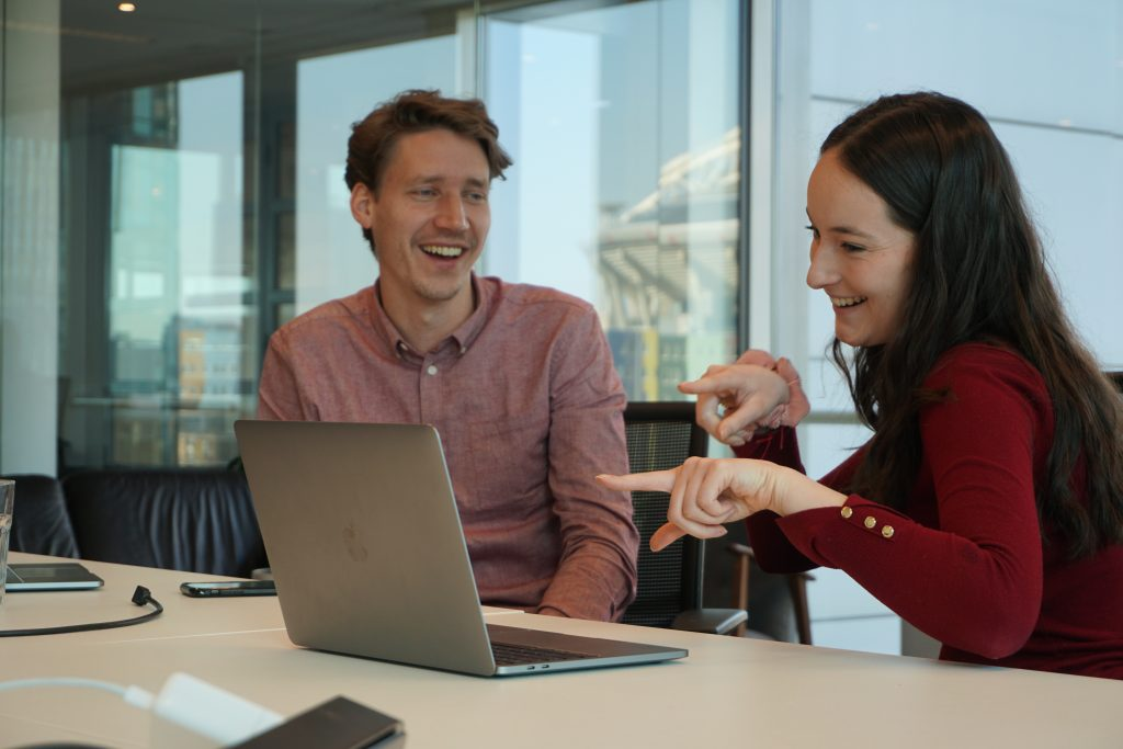people laughing in front of a computer