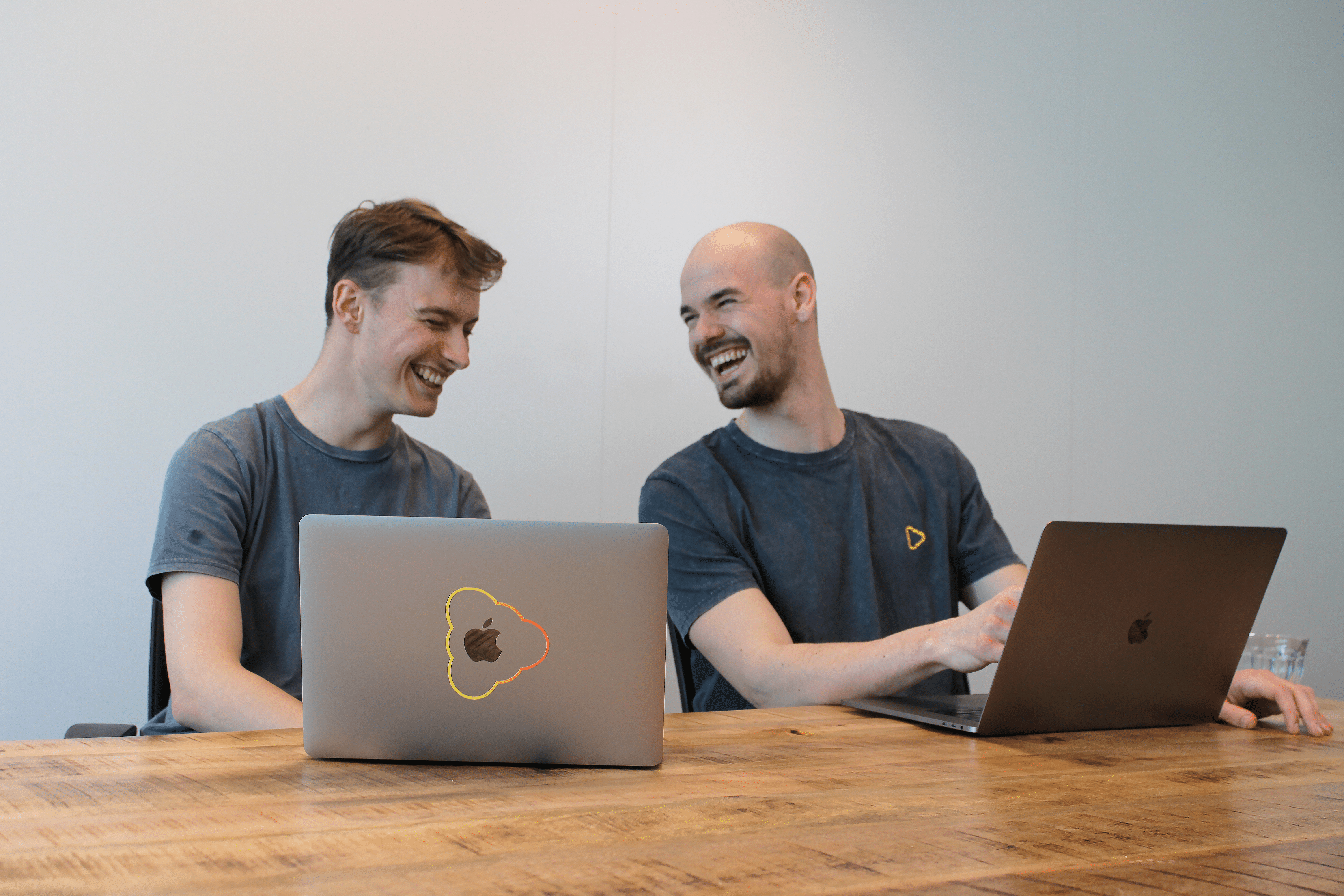 men laughing with 2 computers