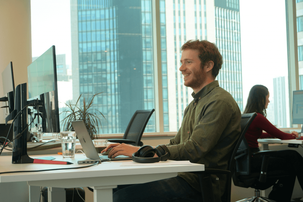 man sitting in front of the computer and smiling